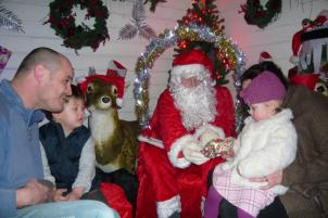 Santa handing out a present at Santa\'s Grotto at Sidmouth Garden Centre - December 2009